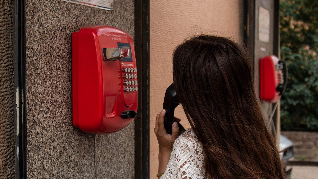 Woman using red telephone
